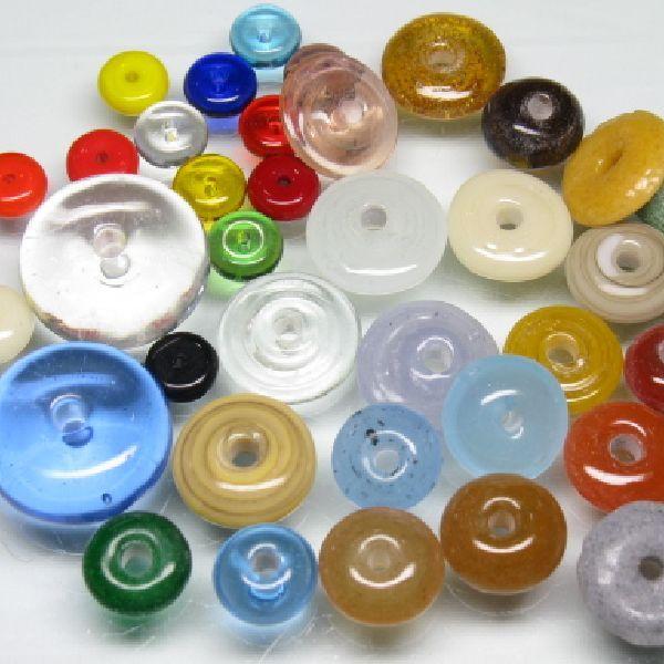 単色のボタン型(円盤型)のとんぼ玉です。熱帯ジャワの工房でバーナーワークによるすべて手作りのため形状のばらつきが大きい品番です。