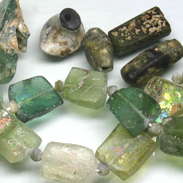 アフガニスタン産のローマングラスビーズです。ローマ時代に作られたガラス瓶などの破片が長い間土中に埋もれて土中の成分とガラス表面が反応して、細かい凹凸により光を乱反射することで虹色の光沢をもつ、いわゆる銀化した状態で出土したガラスの破片を整形し、穴を開けてビーズに加工したものです。弊店のローマングラスはアフガニスタン・バーミヤ-ン近郊で出土したものです。