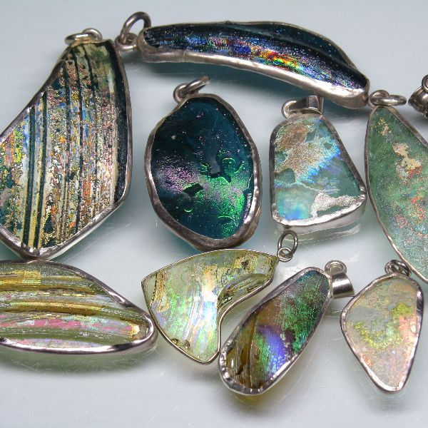 アフガニスタンで出土したガラス瓶などの破片と思われる透明感のある板状のローマングラスにシルバー925で彫金を施したたいへん美しいペンダントトップです。ローマ時代に作られたガラス瓶などの破片が長い間土中に埋もれて土中の成分とガラス表面が反応して、細かい凹凸により光を乱反射することで虹色の光沢をもつ、いわゆる銀化した状態で出土したガラスの破片にシルバー925で縁取り下ものです。ローマングラスはアフガニスタン・バーミヤ-ン近郊で出土したものです。