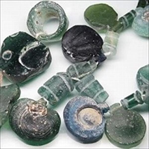 アフガニスタン産のローマングラスビーズを連に仕立てたものです。ローマ時代に作られたガラス瓶などの破片が長い間土中に埋もれて土中の成分とガラス表面が反応して、細かい凹凸により光を乱反射することで虹色の光沢をもつ、いわゆる銀化した状態で出土したガラスの破片を整形し、穴を開けてビーズに加工したものです。弊店のローマングラスはアフガニスタン・バーミヤ-ン近郊で出土したものです。